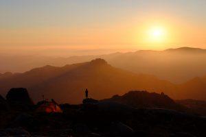 Pessoa a acampar e a ver o pôr do sol